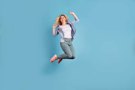 Full body photo of pretty lady raising arms wearing pants trousers isolated over blue background