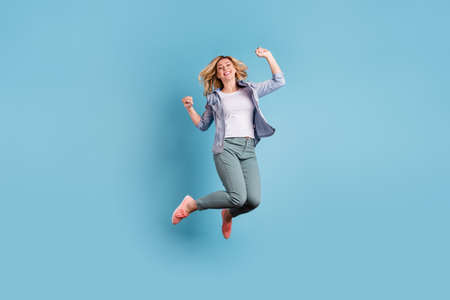 Full size photo of cute pretty woman jumping raising fists wearing pants trousers isolated over blue background Banco de Imagens