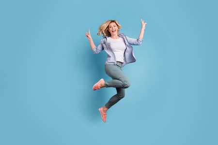 Full size photo of cheerful person jumping moving making v-signs laughing isolated over blue background