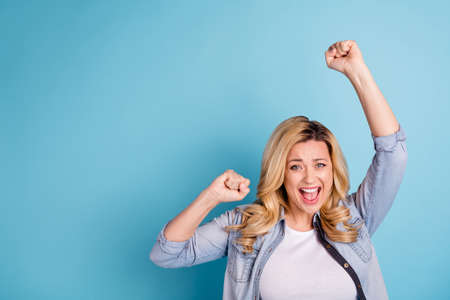 Portrait of cheerful cute lady shouting yeah raising fists isolated over blue background Banque d'images
