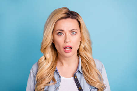 Close up photo of astonished lady with opened mouth looking isolated over blue background