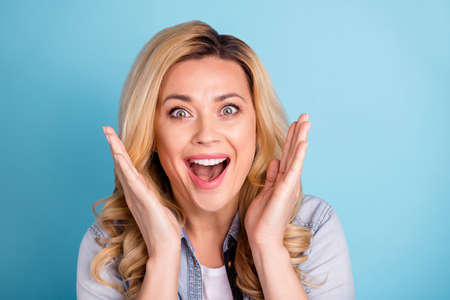 Close up photo of cheerful excited woman shouting yelling opening mouth isolated over blue background 写真素材