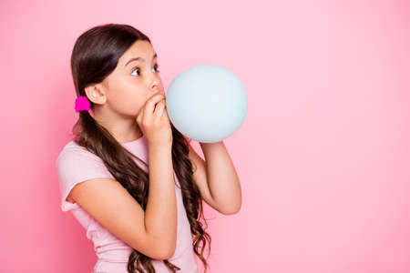Profile side photo of cute kid hold baloon inflate look dressed white t-shirt isolated over pink background