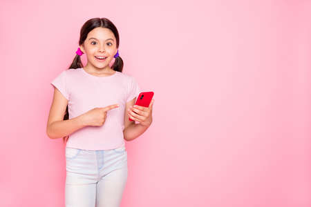 Portrait of excited kid with ponytails pigtails holding gadget screaming indicating dressed trendy stylish t-shirt pants trousers isolated over pink background Stock Photo