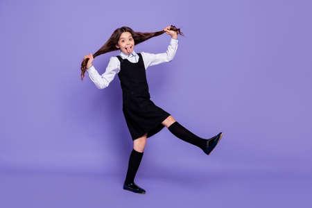 Vista a tutta lunghezza delle dimensioni del corpo di lei lei bella attraente bella allegra allegra felice spensierata ragazza pre-adolescente dai capelli ondulati che fa code divertendosi tempo isolato su sfondo viola brillante brillante brillante