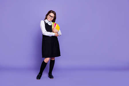 Full length body size view of nice attractive cheerful intelligent wavy-haired pre-teen girl ready to class holding in hands academic, literature isolated over bright vivid shine violet background