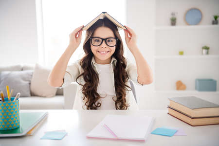Portrait of her she nice attractive charming cute intelligent cheerful cheery foolish wavy-haired pre-teen girl holding book on head like roof class work in light white interior room library indoors