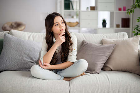 Portrait of her she nice-looking attractive lovely charming cute calm wavy-haired pre-teen girl sitting on divan thinking in light white interior living-room house indoors