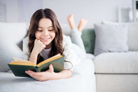 Portrait of her she nice attractive lovely charming cute cheerful cheery focused wavy-haired preteen girl lying on divan reading novel in light white interior living-room indoors