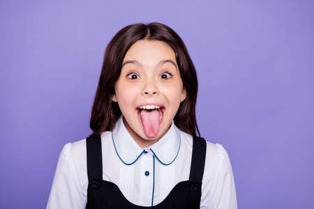 Close-up portrait of her she nice attractive cheerful cheery naughty wavy-haired pre-teen girl showing tongue out having fun isolated over bright vivid shine violet background Stockfoto