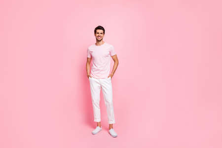 Full length body size view portrait of his he nice attractive lovely cheerful cheery content guy posing holding hands in pockets isolated over pink pastel background