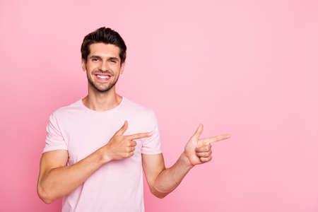 Portrait of his he nice attractive cheerful cheery confident content guy pointing two forefingers aside promotion surprise ad advert isolated over pink pastel background Stockfoto