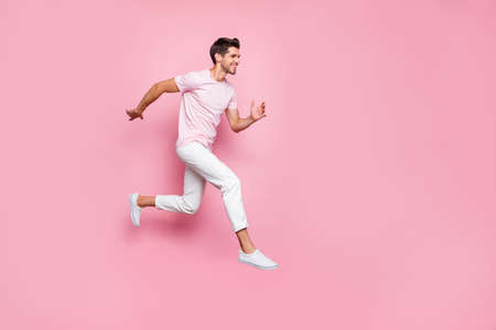 Full size profile side photo of attractive person running smiling isolated over pink background 写真素材
