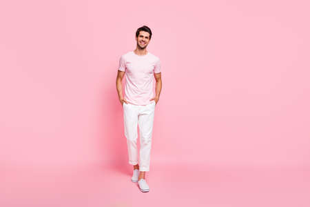 Full length body size view portrait of his he nice attractive lovely groomed cheerful cheery content guy walking posing holding hands in pockets isolated over pink pastel background Stock Photo