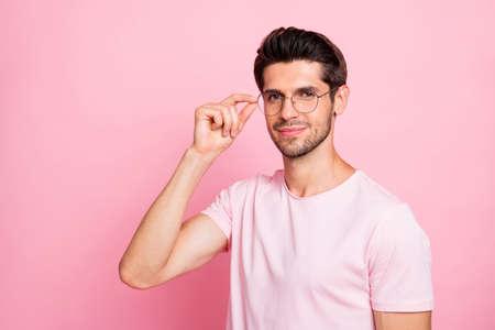 Portrait en gros plan de son beau mec intelligent et beau contenu rêveur portant des spécifications rondes isolées sur fond pastel rose