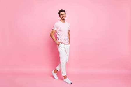 Full length body size view portrait of his he nice attractive lovely content cheerful cheery successful guy walking holding hands in pockets isolated over pink pastel background Stock Photo
