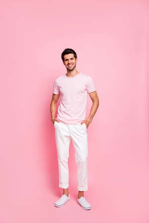 Vertical full length body size view portrait of his he nice attractive lovely content cheerful cheery glad successful guy posing holding hands in pockets isolated over pink pastel background