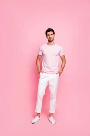 Vertical full length body size view portrait of his he nice attractive lovely content cheerful successful guy holding hands in pockets isolated over pink pastel background Stock Photo