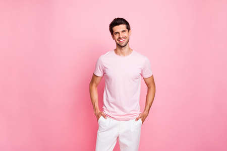 Portrait of his he nice attractive lovely content cheerful cheery glad successful guy holding hands in pockets isolated over pink pastel background