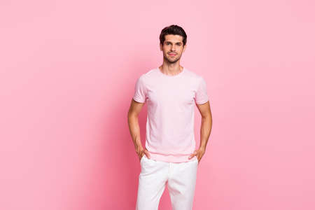 Portrait of his he nice attractive lovely handsome content successful guy holding hands in pockets isolated over pink pastel background