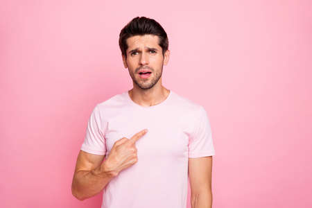Portrait of his he nice attractive lovely confused guy pointing at him self wrong solution decision isolated over pink pastel background