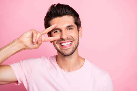 Closeup photo of amazing guy send friends v-sign symbol near eye wearing casual outfit isolated on pink background Фото со стока