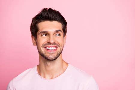 La foto del primo piano di un ragazzo fantastico sembra uno stupido spazio vuoto che indossa abiti casual isolati su sfondo rosa