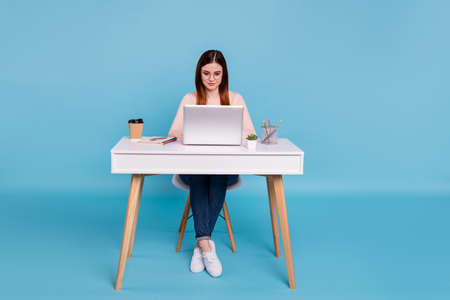 Portrait of nice attractive concentrated focused girl sitting on a chair 스톡 콘텐츠