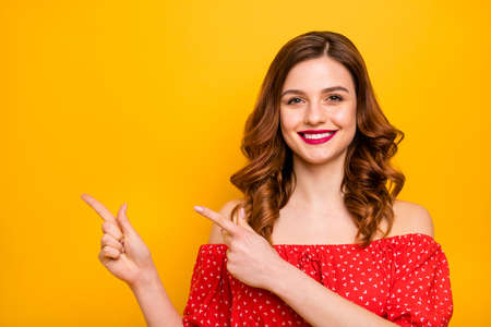 Photo of a lady wearing red dress with open shoulders isolated yellow background 写真素材 - 128606624