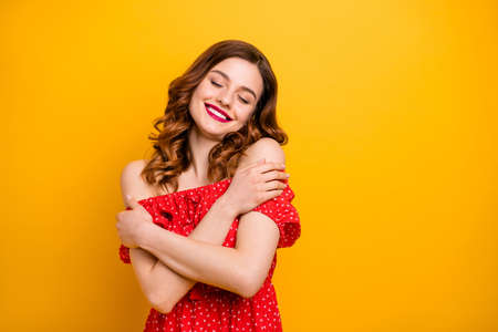 Photo of a lady wearing red dress with open shoulders isolated yellow background Stock Photo