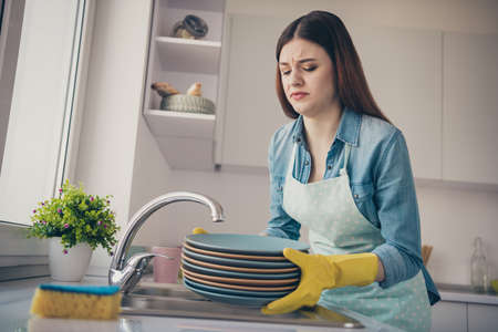Photo of house wife displeased working alone tired carry heavy dishes wear dotted apron bright kitchen Stockfoto - 128606667