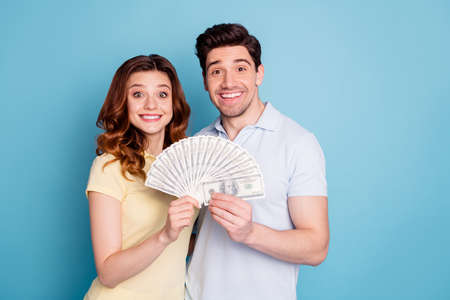 Portrait of his he her she nice attractive cheerful cheery funny people holding in hands hundreds loan credit win winner isolated over bright vivid shine blue green background Stock fotó