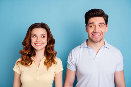 Close up photo of two people funky mood look each other silly expression rumours wear casual t-shirts isolated blue background