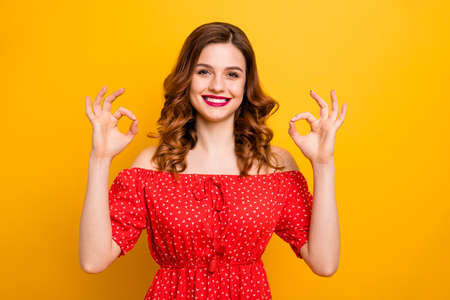 Photo of a lady wearing red dress with open shoulders isolated yellow background 写真素材