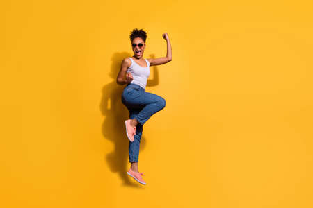 Photo of a happy dark skin lady wearing casual jeans denim pants and tank-top isolated bright yellow background Stock Photo - 128611138