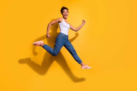 Photo of a happy dark skin lady wearing casual jeans denim pants and tank-top isolated bright yellow background Stock Photo - 128611141