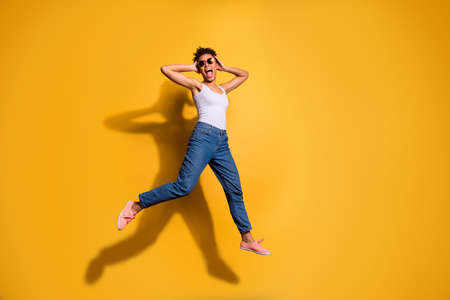 Photo of a happy dark skin lady wearing casual jeans denim pants and tank-top isolated bright yellow background Stock Photo - 128611144