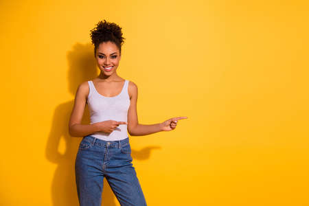 Photo of a happy dark skin lady wearing casual jeans denim pants and tank-top isolated bright yellow background Stock Photo - 128611145