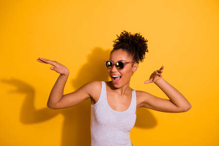 Photo of a happy dark skin lady wearing casual jeans denim pants and tank-top isolated bright yellow background Stock Photo