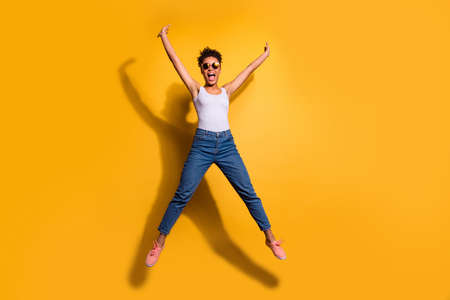 Photo of a happy dark skin lady wearing casual jeans denim pants and tank-top isolated bright yellow background Stock Photo - 128611188