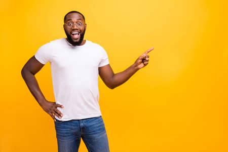 Young guy with dark skin wearing casual outfit on yellow background