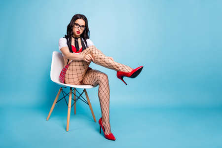 Nice-looking attractive lovely slim fit alluring gorgeous confident wavy-haired lady sitting on chair fixing hosiery isolated on bright vivid shine blue green turquoise background Фото со стока