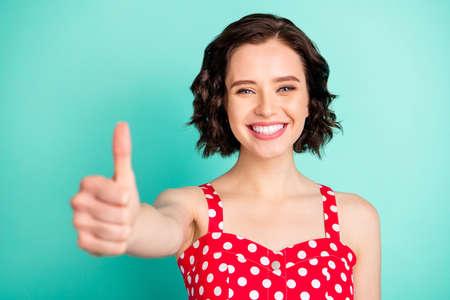 Portrait en gros plan d'une charmante fille joyeuse et ravie, levant le pouce afin de vous montrer son opinion sur vos différents résultats tout en étant isolée sur fond bleu sarcelle