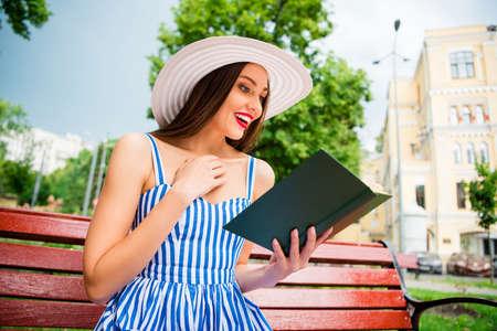 Hübsche Dame, die eine unglaublich interessante Geschichte liest, wundert sich über das Ende des gemütlichen Brunchs, trägt Sonnenhut und Kleid Standard-Bild