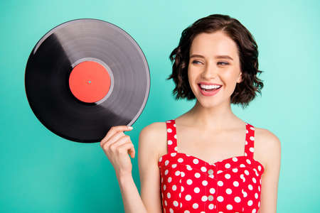 Photo of nice cute encouraged cheerful girlfriend thinking on where she can listen to music recorded in this plate while isolated with teal background