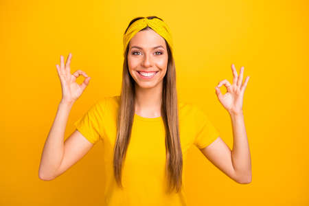 Portrait of lovely millennial showing double okay sign with beaming amile isolated over yellow background