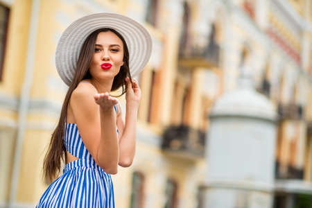 Photo of amazing lady walking down paris street sending boyfriend air kiss wear sun hat and striped dress