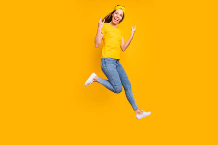 Full body photo of beautiful lady jumping high rejoicing at metal concert wear casual clothes isolated yellow background
