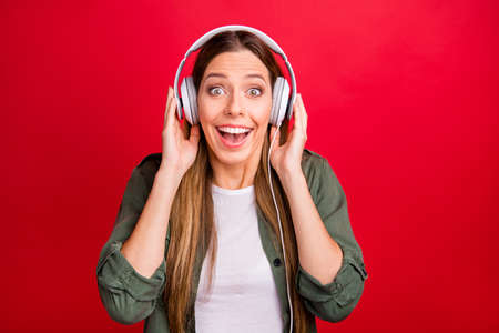 Photo of funny surprised charming beautiful attractive girl listening to new album of her favorite artist while isolated with red background Stock Photo