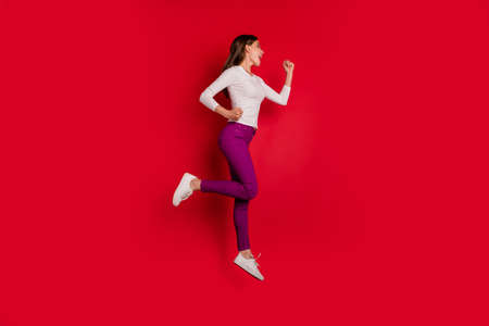 Full length body size photo of joyful encouraged nice cute girlfriend running towards shopping mall because there are discounts while isolated with red background